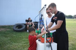 kids serve players at practice